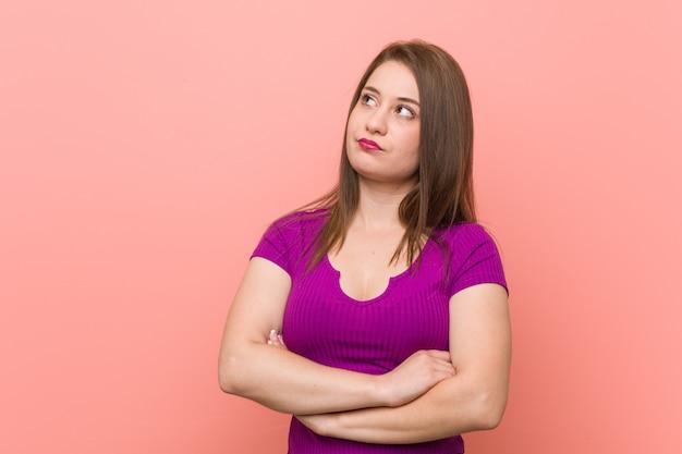 Mulher latino-americano nova contra uma parede cor-de-rosa cansado de uma tarefa repetitiva.