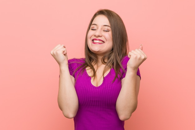 Mulher latino-americano nova contra uma parede cor-de-rosa que levanta o punho, sentindo feliz e bem sucedido. conceito de vitória.