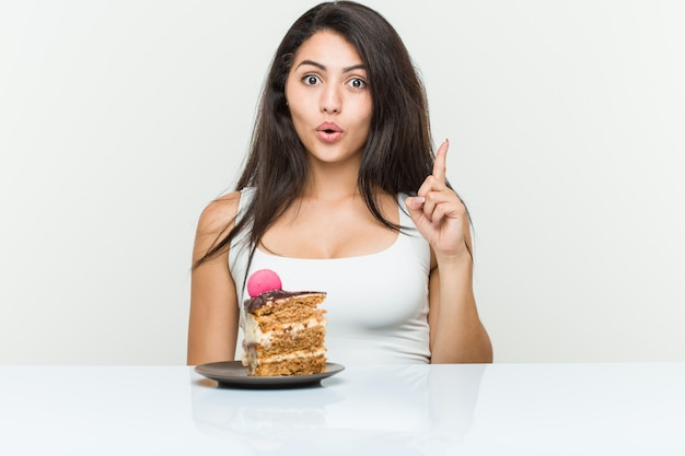 Mulher latino-americano nova que come um bolo que tem alguma grande ideia, conceito da faculdade criadora.