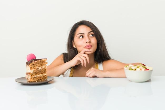 Mulher latino-americano nova que escolhe entre o bolo ou a fruta que olha lateralmente com expressão duvidosa e cética.
