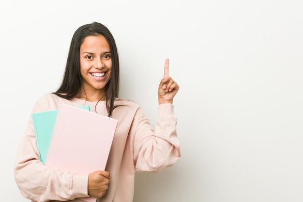 Mulher latino-americano nova que guarda alguns cadernos que sorriem alegremente apontando com o dedo indicador afastado.