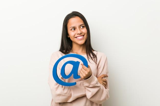 Mulher latino-americano nova que guarda no sorriso do ícone seguro com braços cruzados.