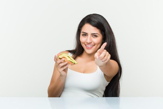 Mulher latino-americano nova que guarda sorrisos alegres de um brinde do abacate que aponta à parte dianteira.