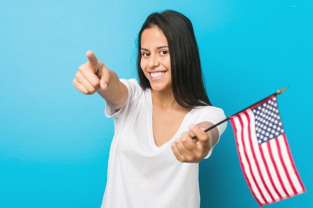 Mulher latino-americano nova que guarda sorrisos alegres de uma bandeira de estados unidos que apontam para a parte dianteira.