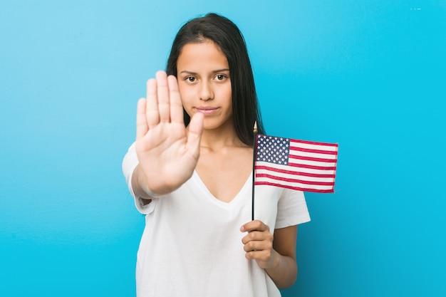 Mulher latino-americano nova que guarda uma bandeira de estados unidos que está com a mão estendida que mostra o sinal de parada, impedindo-o.