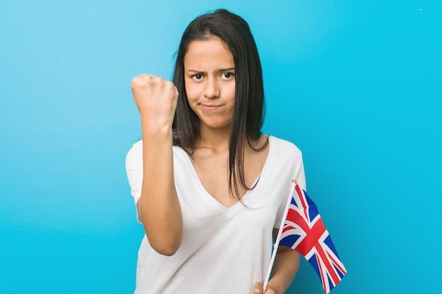 Mulher latino-americano nova que guarda uma bandeira de reino unido que mostra o punho à câmera, expressão facial agressiva.