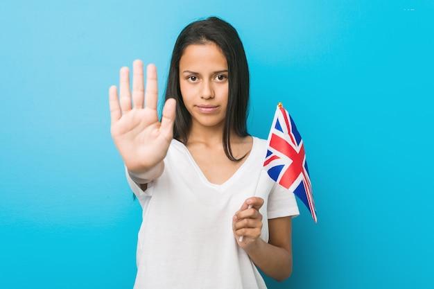Mulher latino-americano nova que guarda uma bandeira do reino unido que está com a mão estendida que mostra o sinal de parada, impedindo-o.