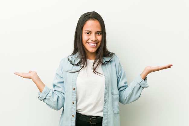 Mulher latino-americano nova que mostra uma expressão bem-vinda.