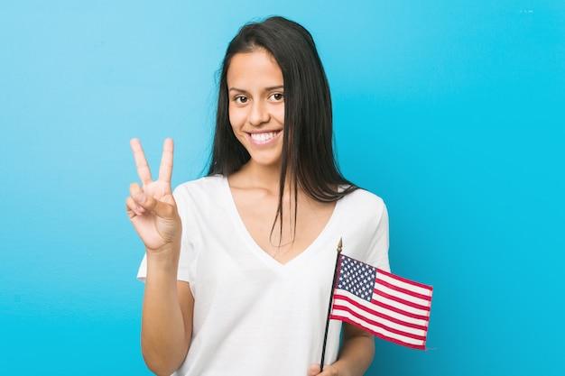 Mulher latino-americano nova que prende uma bandeira de estados unidos que mostra o número dois com dedos.