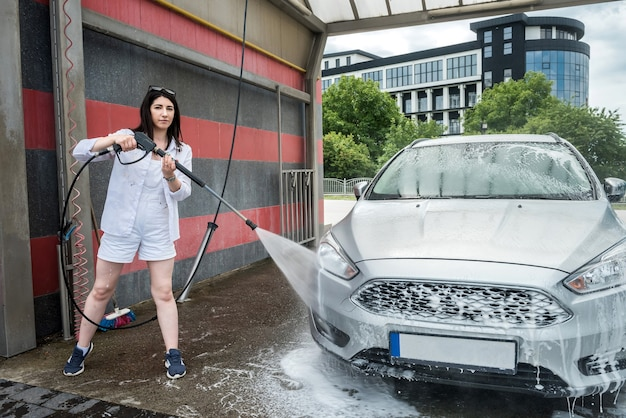 Mulher lava a espuma com água no carro, limpando e lavando o carro. serviço