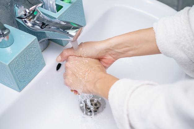 Mulher lava a mão na pia do banheiro, sem rosto