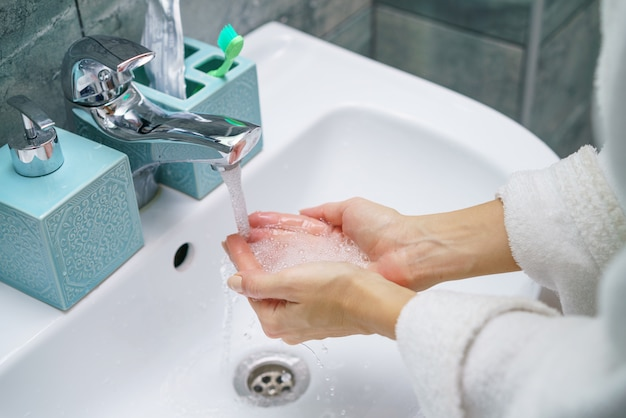 Mulher lava a mão na pia do banheiro