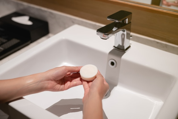 Mulher lava as mãos com sabão na pia com água.