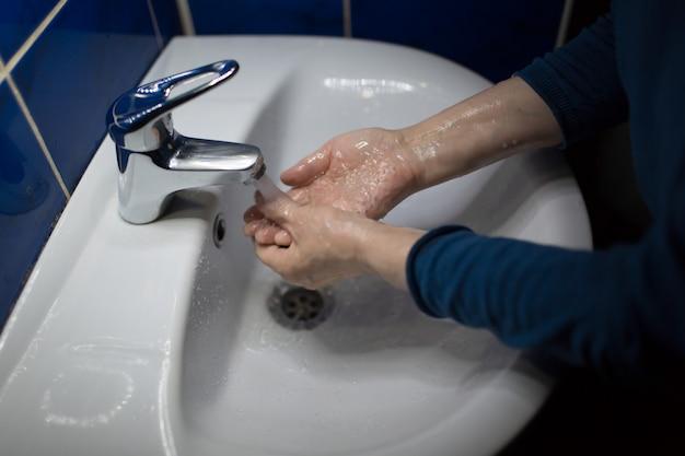 Mulher lava as mãos com sabão sob a torneira de água. prevenção e lavagem de coronavírus. regras de higiene pandêmica covid-19.
