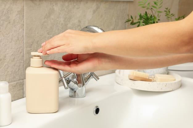 Mulher lava as mãos com sabonete líquido na pia com acessórios de higiene pessoal