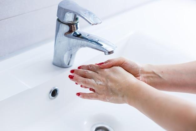Mulher lava as mãos lavatório branco