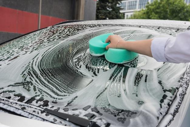 Mulher lava o carro com esponja e espuma
