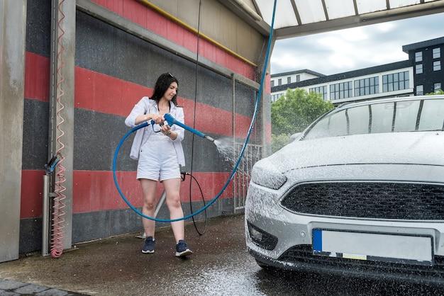 Mulher lava o carro com pistola de água e tira a espuma. auto-limpeza