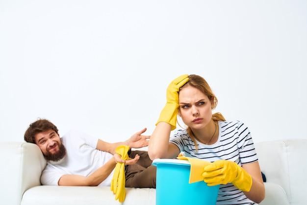 Mulher lava o chão enquanto o homem se senta no sofá