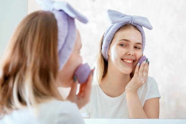 Mulher lava o rosto com esponja natural e espuma cosmética esfoliante de sabão no reflexo do retrato do banheiro no espelho. loira adolescente faz a rotina matinal de autocuidado. estilo de vida cosmético de cuidado de pele.