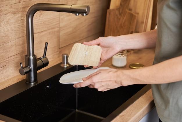 Mulher lava pratos com esponja ecológica orgânica. conceito de desperdício zero