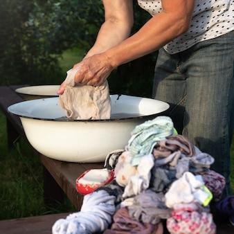 Mulher lava roupas com as mãos em uma bacia velha com sabonete ao ar livre