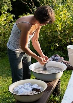 Mulher lava roupas com as mãos na velha bacia ao ar livre no campo na noite de verão