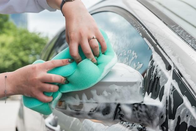 Mulher lava um carro com uma esponja com espuma