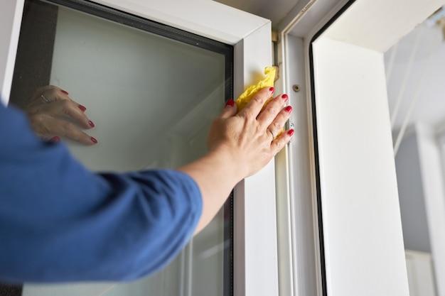 Mulher lava uma armação de metal-plástico de uma janela aberta