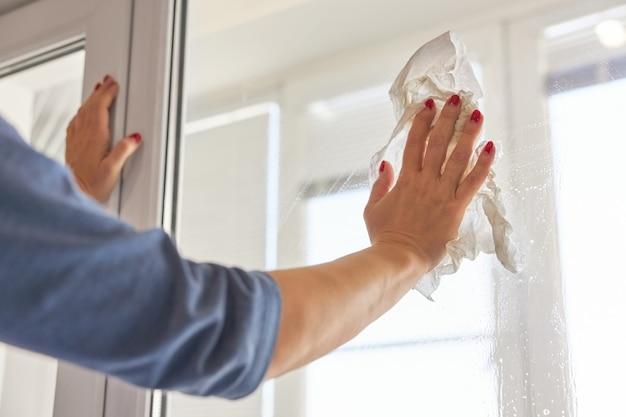 Mulher lava vidro usando uma toalha de papel
