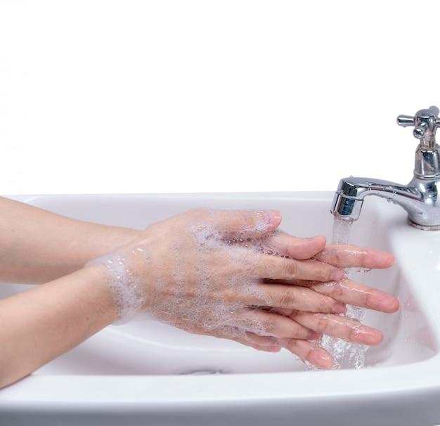 Mulher lavando a mão com espuma de sabão e água da torneira no banheiro.