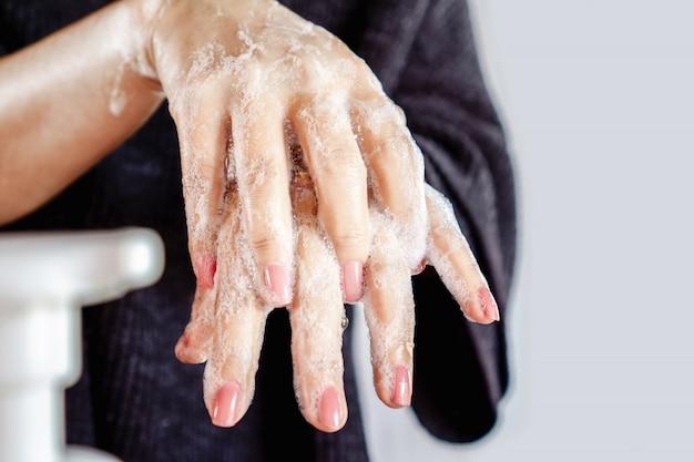 Mulher lavando a mão com sabão