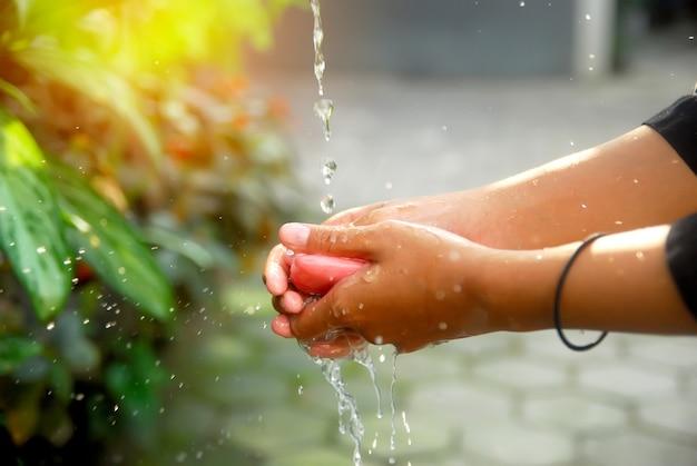 Mulher lavando as mãos com água e sabão