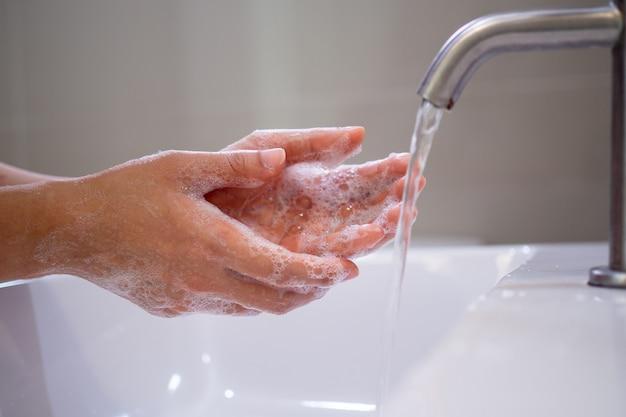 Mulher lavando as mãos com sabão conceito de higiene para limpeza das mãos