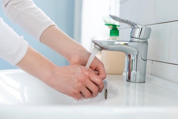 Mulher lavando as mãos dentro de casa