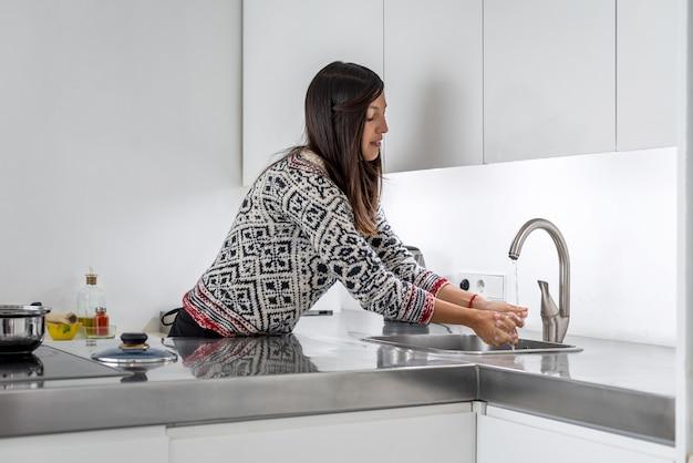Mulher lavando as mãos depois de cozinhar