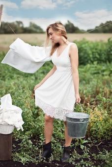 Mulher lavando as mãos e pendurando roupas ao ar livre em um dia ensolarado