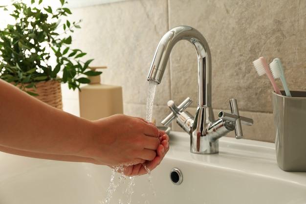 Mulher lavando as mãos embaixo da torneira da pia