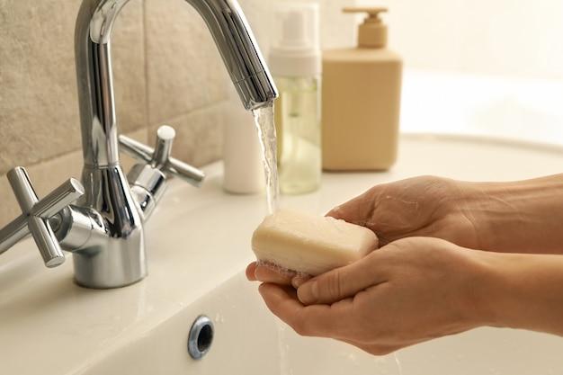 Mulher lavando as mãos na pia do banheiro com sabonete