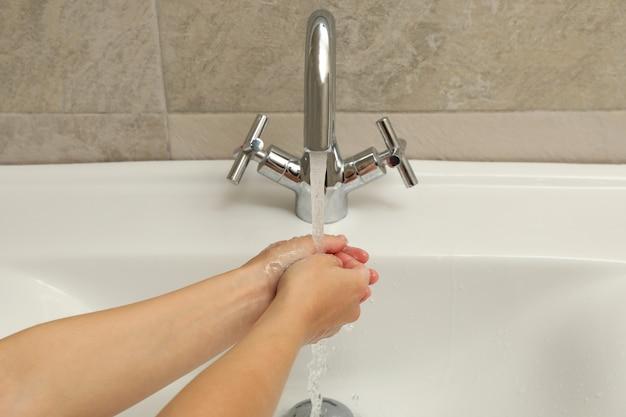 Mulher lavando as mãos na pia