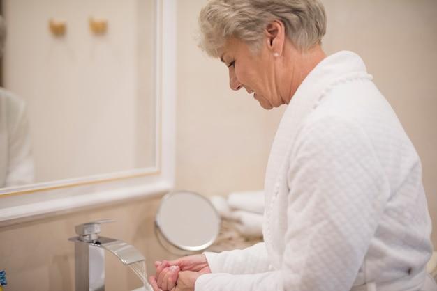 Mulher lavando as mãos no banheiro