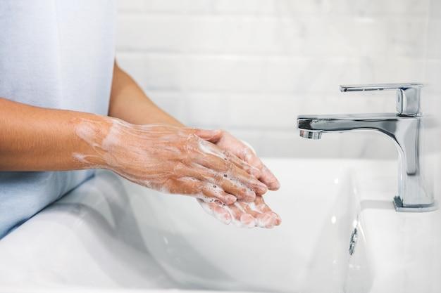 Mulher lavando as mãos para evitar a propagação do coronavirus, bem como resfriado, gripe, bactérias em casa