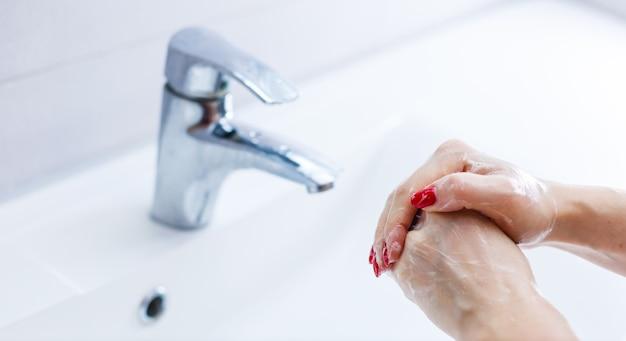 Mulher lavando as mãos sobre fundo branco