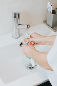 Mulher lavando as peças de sua escova de dente elétrica com água depois de escovar os dentes