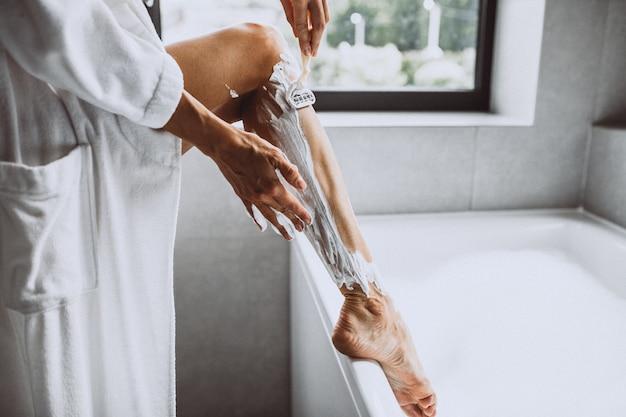 Mulher lavando as pernas em casa no banheiro