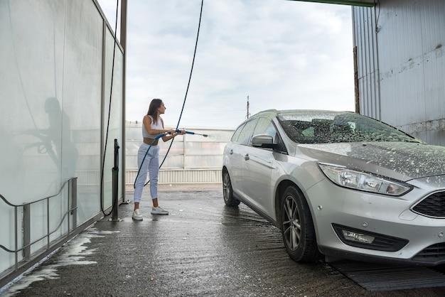 Mulher lavando automóvel com mangueira
