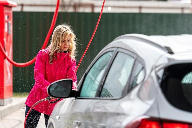 Mulher lavando carro com lavadora de alta pressão em posto de lavagem de carros self-service, foco seletivo