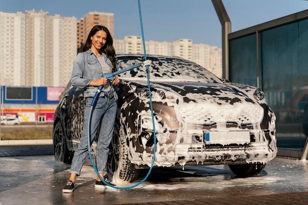 Mulher lavando carro lá fora