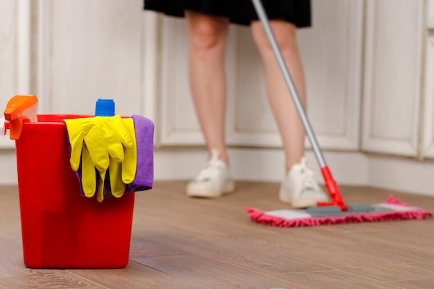 Mulher lavando chão com esfregão na cozinha