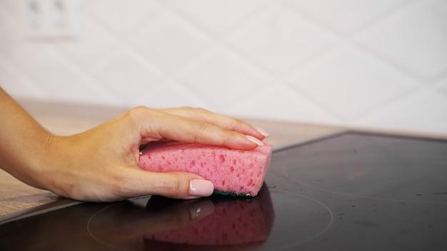 Mulher lavando fogão elétrico à mão na cozinha moderna